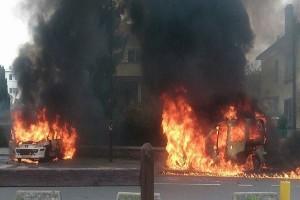 agresivní útočníci obklíčili policejní auto, v němž seděli čtyři policisté, a to auto zapálili